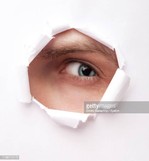 close-up portrait of man looking torn white paper - peeping holes ストックフォトと画像