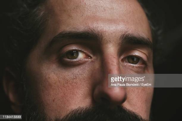 close-up portrait of man over black background - close up stock pictures, royalty-free photos & images