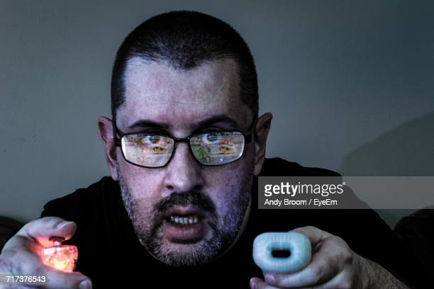 close-up portrait of man playing video game at home - concentration stock pictures, royalty-free photos & images