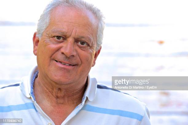 close-up portrait of man smiling while standing outdoors - antonella di martino foto e immagini stock