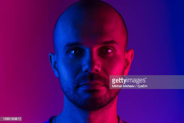 close-up portrait of man standing in illuminated room - illuminated stock pictures, royalty-free photos & images