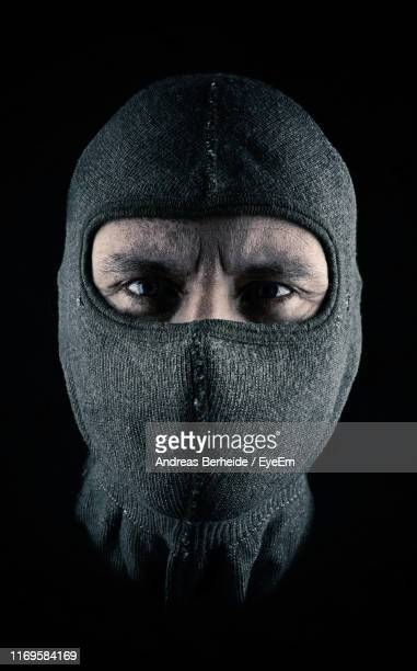 close-up portrait of man wearing mask against black background - balaclava stock pictures, royalty-free photos & images
