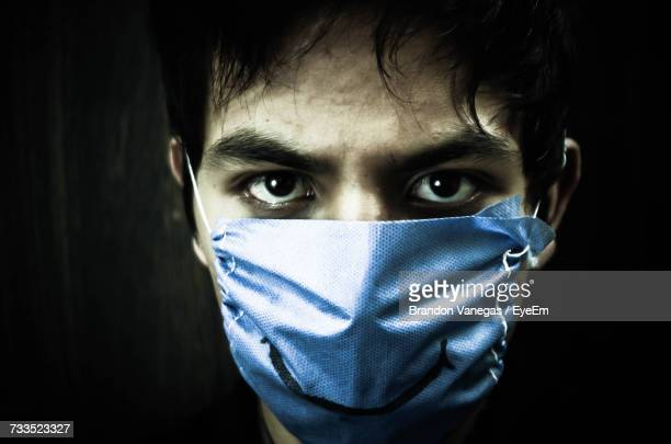 Close-Up Portrait Of Man Wearing Pollution Mask With Smiling Sign