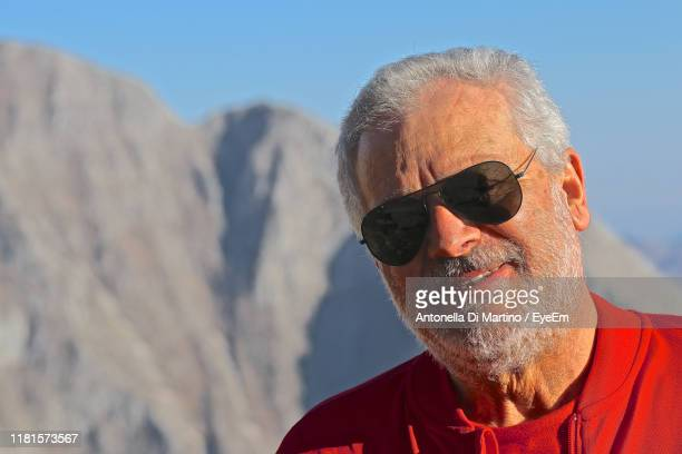 close-up portrait of man wearing sunglasses against mountain - antonella di martino foto e immagini stock