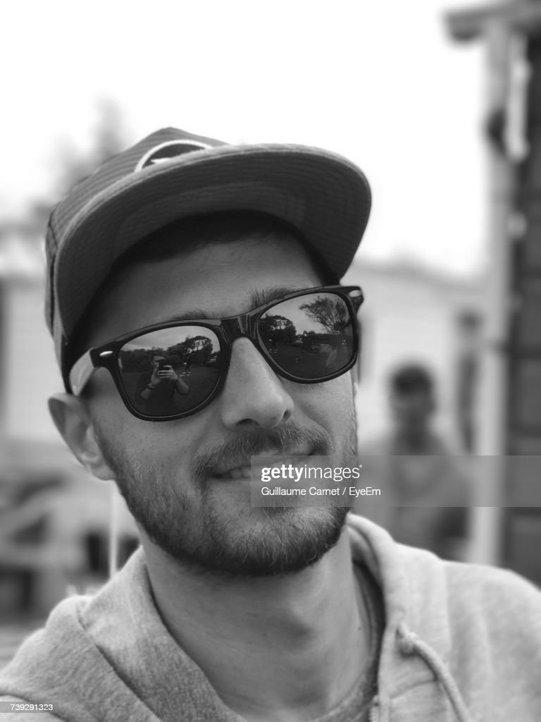63fca42dad81 Close-Up Portrait Of Man Wearing Sunglasses And Cap Outdoors - stock photo