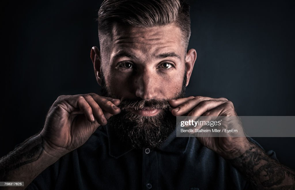 Close-Up Portrait Of Man With Mustache Against Black Background : Stock Photo