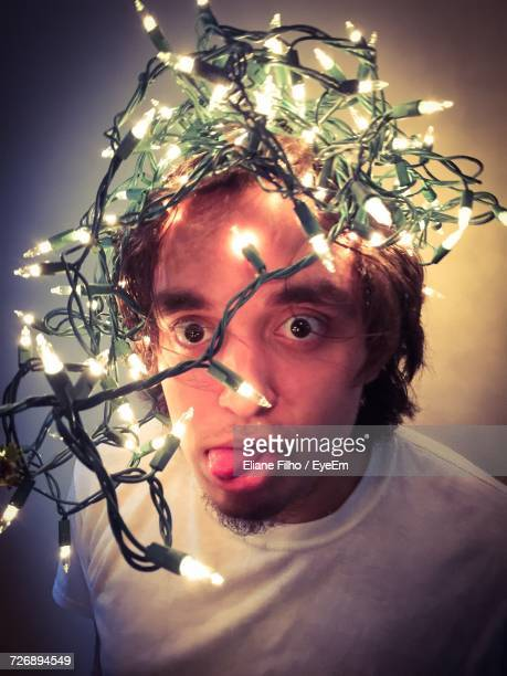 close-up portrait of man with string lights against wall - filho stock pictures, royalty-free photos & images