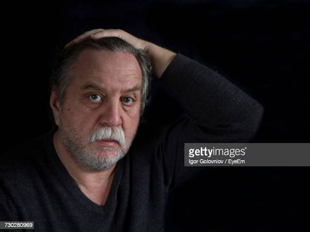 close-up portrait of mature man against black background - igor golovniov stock pictures, royalty-free photos & images