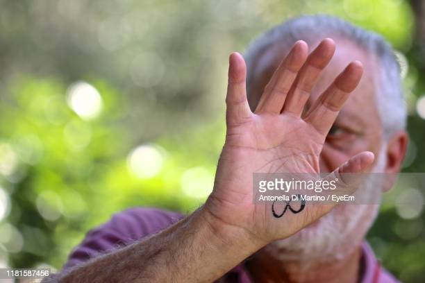 close-up portrait of mature man showing infinity symbol on hand - antonella di martino foto e immagini stock