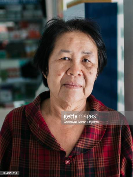 close-up portrait of mature woman standing at home - chanayut stock photos and pictures