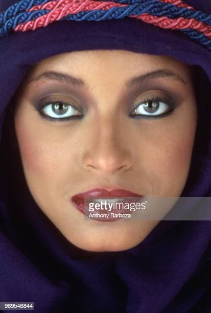 Closeup portrait of model Gay Thomas in a hooded top wrapped with a red and blue cords New York 1970s