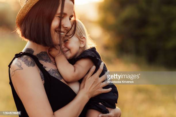 closeup portrait of mother and little daughter playing together in summer park on sunset lights. beauty nature scene with family outdoor lifestyle. happy family concept. - light natural phenomenon stock pictures, royalty-free photos & images