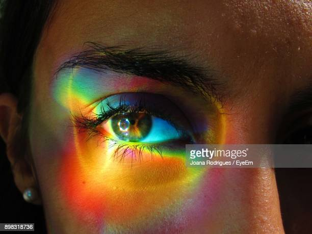 close-up portrait of multicolored light on woman eye - spectrum stock pictures, royalty-free photos & images