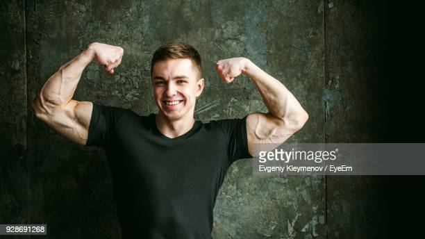 close-up portrait of muscular man flexing muscles by wall - showing off stock photos and pictures