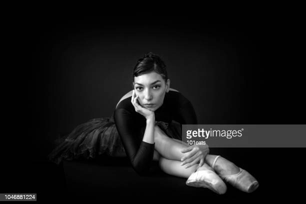 Close-up portrait of professional ballet dancer. She is posing at studio over black background. Art concept