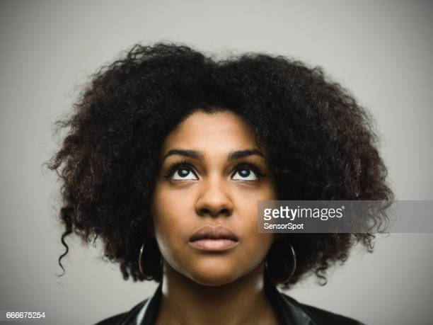 Close-up portrait of real young black woman looking up