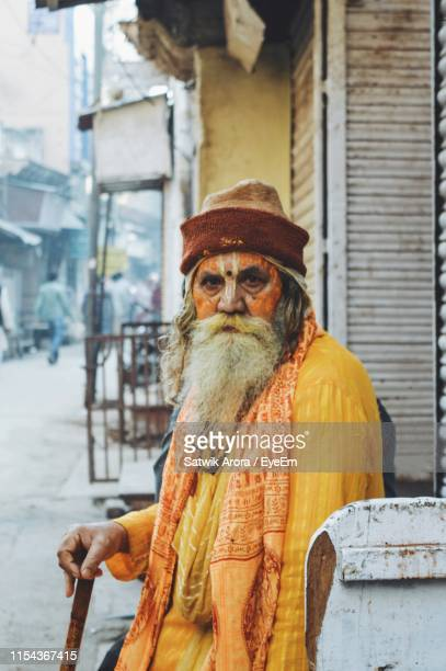close-up portrait of sadhu sitting against built structure in city - punjab - india stock pictures, royalty-free photos & images