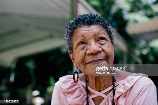 close-up portrait of senior black woman looking thoughtful - differential focus stock pictures, royalty-free photos & images