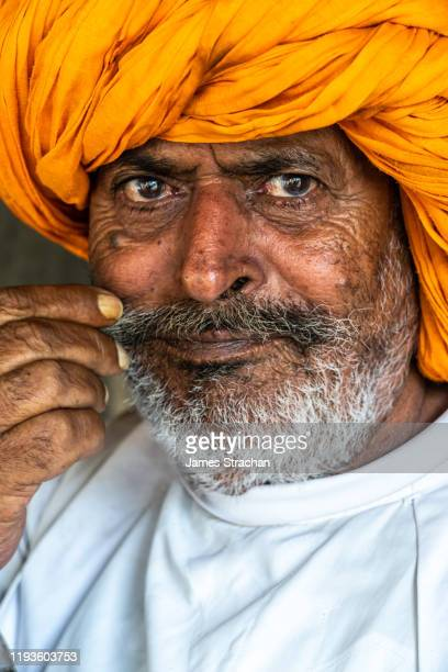 close-up portrait of senior male gujar villager in traditional white tunic and bright orange turban, twiddling his moustache, with a wistful smile, pushkar, rajasthan, india (model release) - james strachan stock pictures, royalty-free photos & images