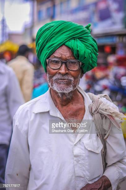 Close-Up Portrait Of Senior Man In Traditional Clothing Walking On Street In Market