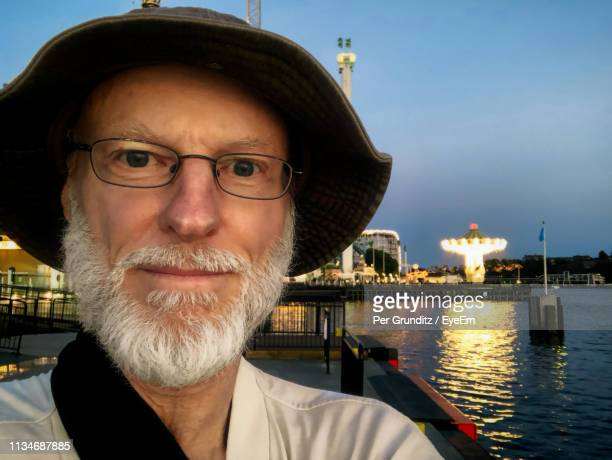 Close-Up Portrait Of Senior Man Wearing Hat Against River In City During Dusk