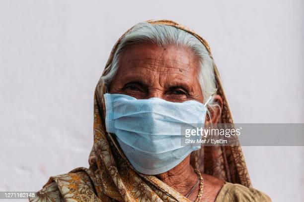 close-up portrait of senior woman wearing mask against white wall - sari stock pictures, royalty-free photos & images