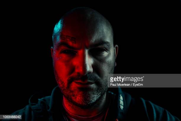 close-up portrait of serious man against black background - criminal stock pictures, royalty-free photos & images