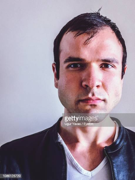close-up portrait of serious man against wall - receding hairline stock pictures, royalty-free photos & images