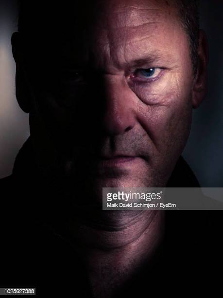 close-up portrait of serious man in darkroom - evil stock pictures, royalty-free photos & images
