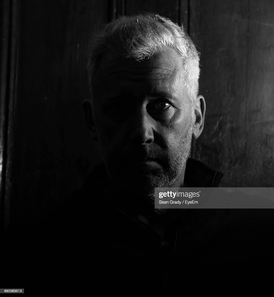 Close-Up Portrait Of Serious Mature Man By Wall In Darkroom : Stock Photo