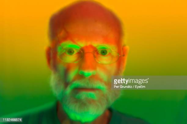 Close-Up Portrait Of Serious Senior Man Wearing Eyeglasses Against Colored Background