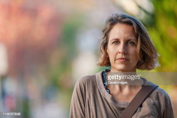 close-up portrait of serious woman standing in park - serious stock pictures, royalty-free photos & images