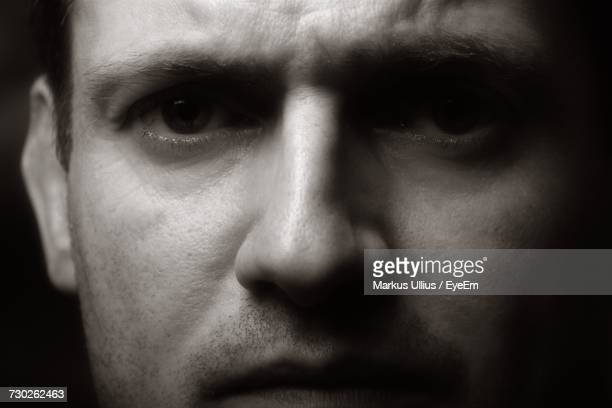 close-up portrait of serious young man against black background - nariz humano imagens e fotografias de stock