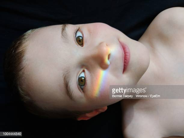Close-Up Portrait Of Shirtless Boy With Rainbow Against Black Backdrop