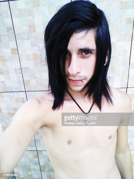 close-up portrait of shirtless emo man standing by tiled wall - emo imagens e fotografias de stock