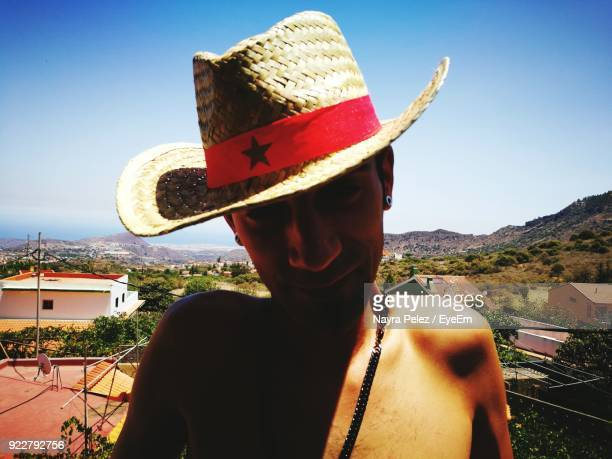 Close-Up Portrait Of Shirtless Man Wearing Hat Against Sky