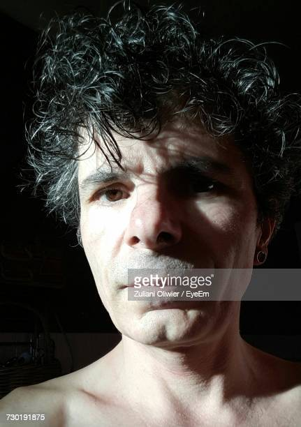 Close-Up Portrait Of Shirtless Man With Curly Hair