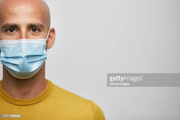 close-up portrait of smiling bald businessman wearing protective face mask. - 30 39 años fotografías e imágenes de stock