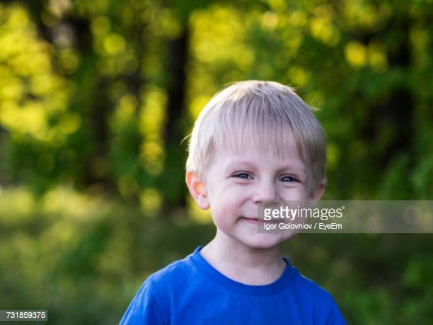 close-up portrait of smiling boy with blond hair at park - igor golovniov stock pictures, royalty-free photos & images