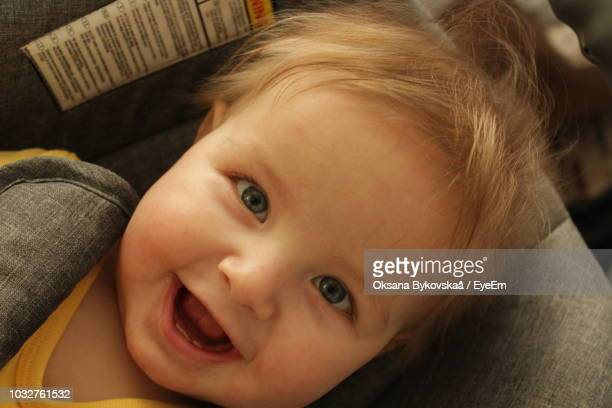 Close-Up Portrait Of Smiling Cute Toddler Boy Lying In Baby Stroller