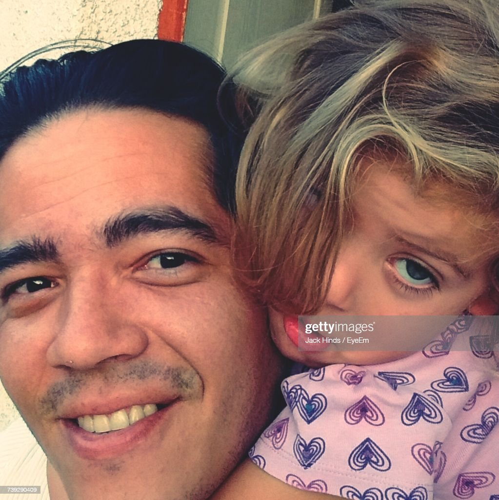 Close-Up Portrait Of Smiling Father With Cute Daughter : Stock Photo