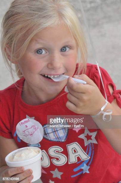 Close-Up Portrait Of Smiling Girl Eating Ice Cream