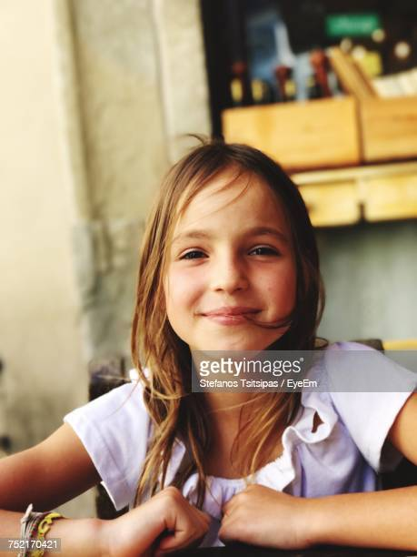 Close-Up Portrait Of Smiling Girl Sitting On Chair At Home