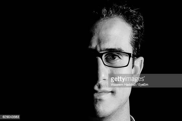 close-up portrait of smiling man against black background - black and white face stock photos and pictures