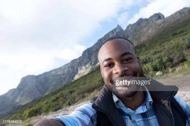 Handsome Man Wearing Santa Hat Taking Selfie High-Res