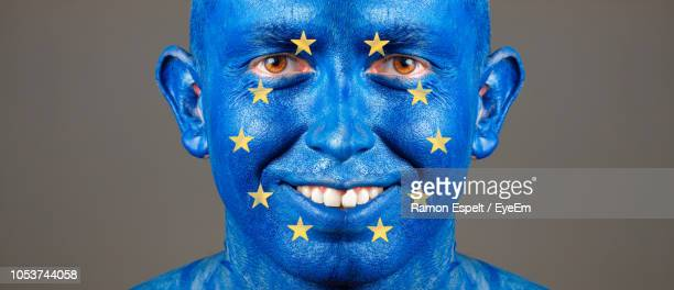 Close-Up Portrait Of Smiling Man With European Union Flag Body Paint Against Gray Background
