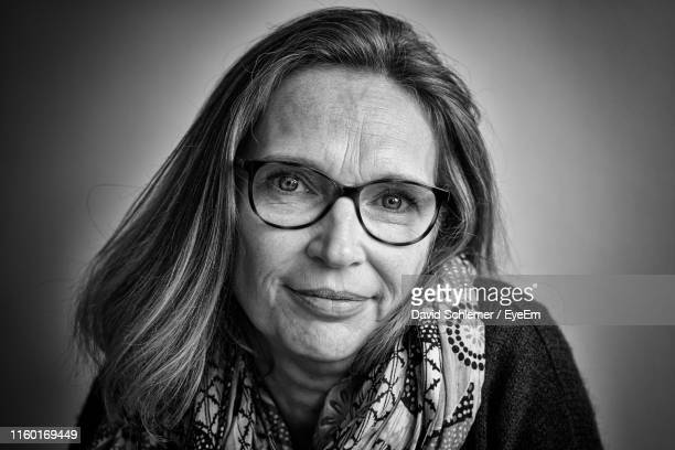 close-up portrait of smiling mature woman wearing eyeglasses - black and white stock pictures, royalty-free photos & images