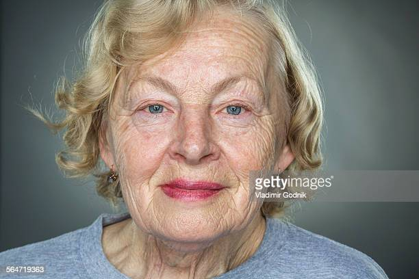 Close-up portrait of smiling senior woman against gray background