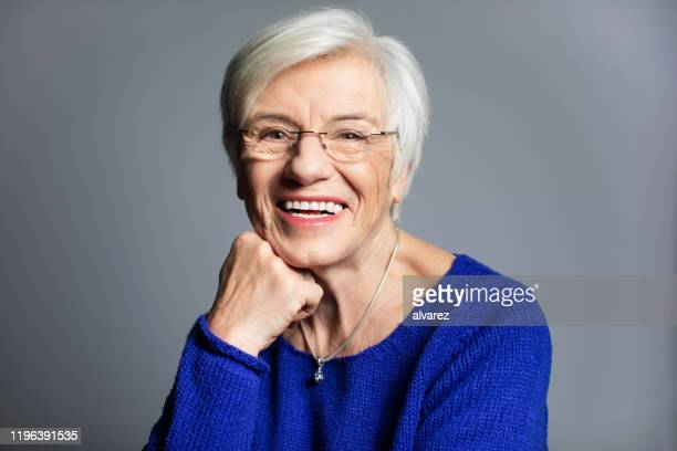 close-up portrait of smiling senior woman - hand on chin stock pictures, royalty-free photos & images