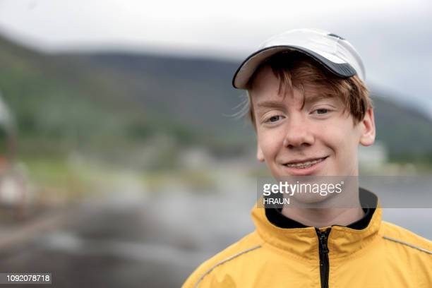 close-up portrait of smiling teenage boy in cap - boys stock pictures, royalty-free photos & images